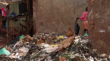 fome : Young African child looking through a rubbish pit in a slum