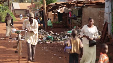 fome : People walking past a rubbish tip in Uganda, Africa