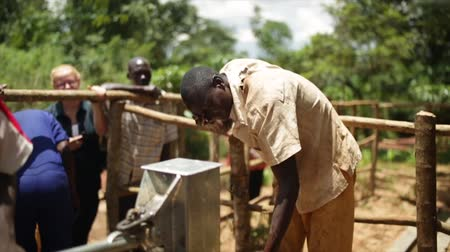 poça de água : An African man washing his face after installing a new well in Uganda, Africa