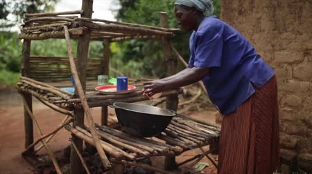 poça de água : An African lady washing dishes outside her kitchen with a wooden draining rack