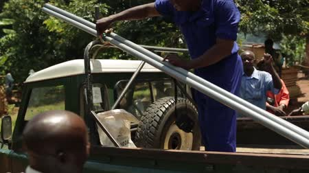 poça de água : An African man in the back of a 4x4 with pipes used to install a new well in rural Uganda, Africa