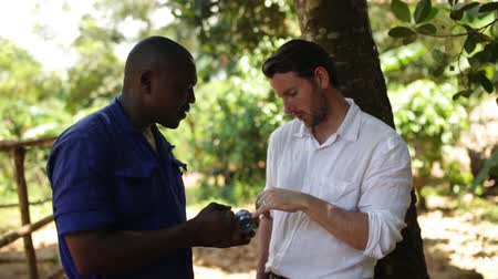 afrika : A caucasian man chatting to African mechanic about the installation of a new well in the village