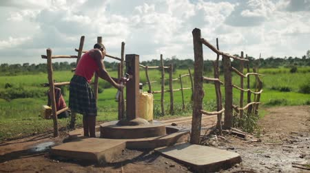 afrika : A young African girl fills a water container by a water pump in a rural part of Uganda, Africa Dostupné videozáznamy