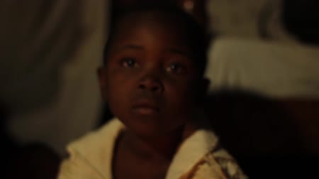 yoksulluk : African child looking at camera in front of kerosene lamp at home Stok Video