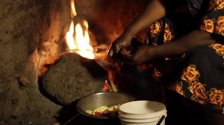 cooking pots : African lady in village perparing food over open fire