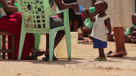 vila : Young African child drinking from a large plastic cup Vídeos