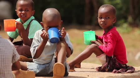 yoksulluk : Young African children drinking from large plastic cups Stok Video