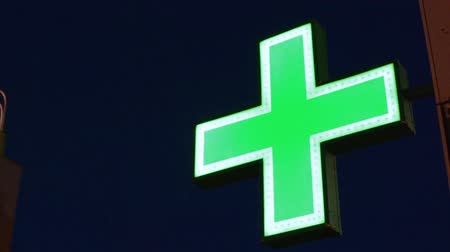Green flashing neon pharmacy cross against a night sky providing a bright symbol of healthcare