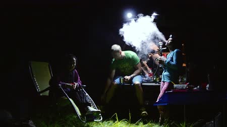 Russian tourists in nature relaxing by smoking a shisha at night time