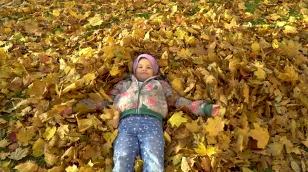 işlemek : A little girl bathes in fallen autumn leaves.