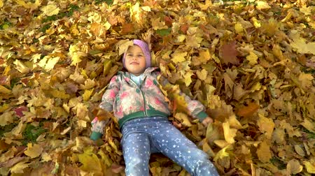 piled up : A little girl bathes in fallen autumn leaves.