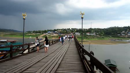Канчанабури : SANGKLABURI ,THAILAND - MAY 2, 2015 : Traveler crossing wooden bridge or Mon Bridge in Sangkha Buri. Kanchanaburi, Thailand. Attractions traditional way of life Стоковые видеозаписи