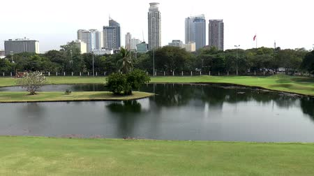 kurs : pan shot of a golf course cityscape elevated view Wideo