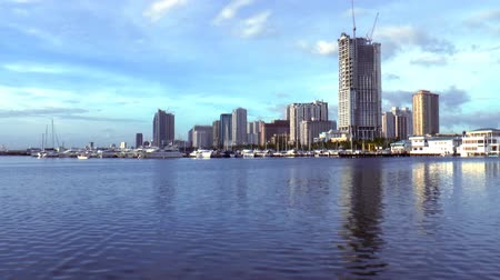 határkő : time lapse footage, video of Manila bay skyline with docked boats and yachts and buildings at the background. Stock mozgókép