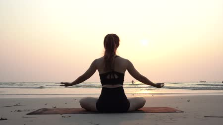 így : Back of views woman practice yoga lotus pose to meditation with summer vacation on the beach feeling so happiness and cheerful,Travel in tropical beach in Thailand,vacations and relaxation Concept