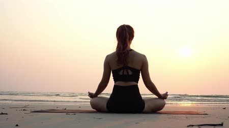 yoğunlaşma : Slow motion of woman practice yoga lotus pose to meditation with summer vacation on the beach feeling so happiness and cheerful,Travel in tropical beach in Thailand,vacations and relaxation Concept