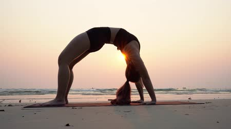 луки : Asian young woman practice Yoga bridge Pose on the sand and beach with sunset beautiful sea in Tropical island, Feel comfortable and relax in holiday, Vacation Yoga Concept Стоковые видеозаписи