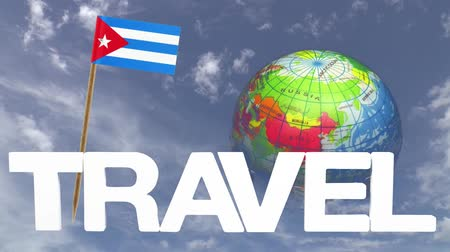 kuba : The word travel and a turning globe  in front of a blue sky with tooth pick and a small paper flag of  CUBA