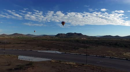Aerial towards hot air balloons landing in desert Wideo