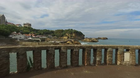 gangplank : Bench overlooking the islet Rocher Du Basta 05 Bench on the islet called Rocher du Basta a beautiful cloudy day on the beach of Biarritz (Dolly Tracking In) Stock Footage