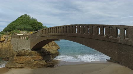 gangplank : Stone bridge to the islet Rocher Du Basta 09 Dolly Truck Left side away from the bridge on the islet called Rocher du Basta a beautiful cloudy day on the beach of Biarritz With swell Stock Footage