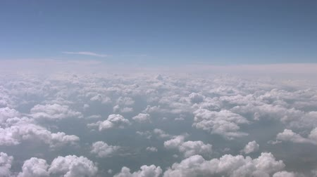 puffy clouds : An aerial view flying above puffy clouds.
