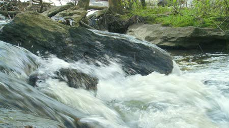 бросаясь : A mountain creek rushes across a large boulder.