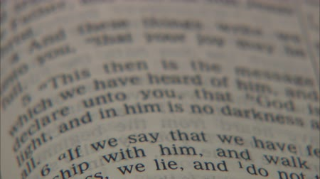 İncil : Panning down the pages of an open Bible. Shallow depth of field focuses on a verse.