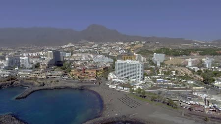 kanarya : TENERIFE, SPAIN? SEPTEMBER 2016: Aerial view of Playa de Las Americas with shore and buildings. Tenerife attracts 5 million tourists annually Stok Video