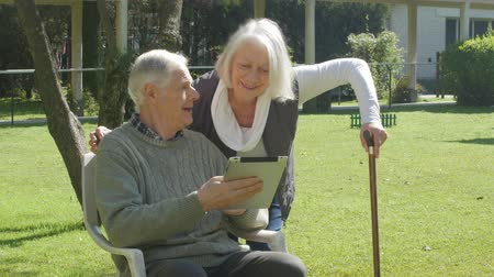 touchpad : Elder couple playing with tablet outdoor