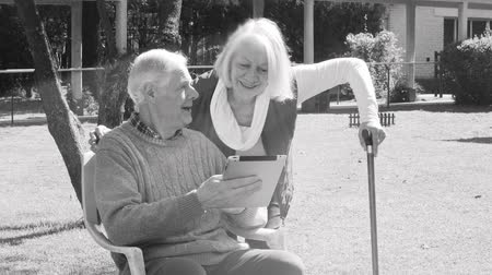 tek renkli : Monochromatic view of elder couple using tablet outdoors with light rays Stok Video