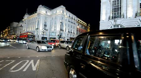 LONDON - JUNE 2015: Piccadilly traffic at night. London attract 15 million tourists annually Stock mozgókép