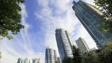 budynki : Highrise Condominium Buildings in Downtown Vancouver BC Canada with Moving White Clouds and Blue Sky Time Lapse 1920x1080