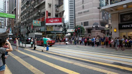 encruzilhada : CAUSEWAY BAY, HONG KONG - MAY 31, 2014: Time lapse of pedestrians and auto traffic crossing busy intersection at Times Square in Causeway Bay Hong Kong. Causeway Bay is a popular tourist destination