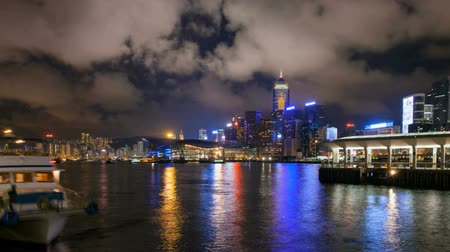 bílé mraky : Time lapse of ferry and moving clouds at Ferry Pier in Victoria Harbour, Hong Kong at night. Locals and tourists alike use the ferries for daily transportation or sightseeing. 1920x1080