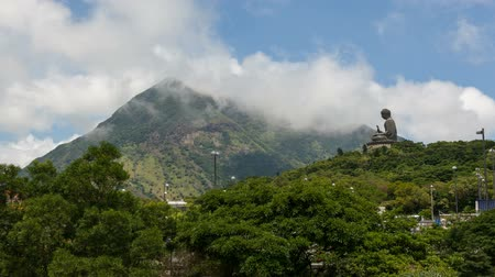 southeast : NGONG PING, HONG KONG - MAY 29, 2014: Time lapse of moving clouds over Tian Tan Big Buddha at Ngong Ping located near Po Lin Monastery. This is a major center of Buddhism in Hong Kong 1920x1080