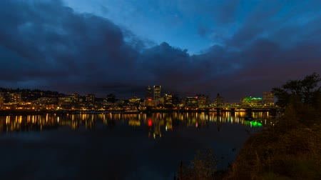 horas : UHD 4k Timelapse movie of moving clouds over Portland Oregon downtown city skyline with Hawthorne Bridge and water reflection along Willamette River at blue hour into night