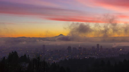 maska : UHD Time Laspe movie of thick rolling fog and low clouds over city of downtown Portland Oregon and snow covered mt. hood one early morning at colorful sunrise during winter season 4096x2304