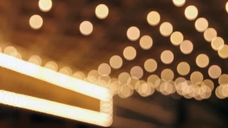 znak : High definition movie of blinking out of focus blurred bokeh concert hall theater lights on broadway along a entertainment street 1080p
