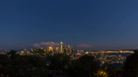 Ultra high definition 4k time lapse movie of clouds and city lights over cityscape and Port of Seattle in Washington state at sunset into blue hour 4096x2304