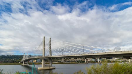 Time lapse of white clouds and blue sky over Portland Oregon with Tilikum Crossing bridge and highway traffic on Marquam Freeway along Willamette River one fall day in autumn season 4k UHD