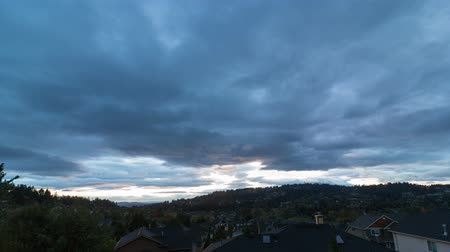 Ultra high definition 4k time lapse movie of moving clouds over residential real estate homes in Happy Valley Oregon at sunset into blue hour 4096x2304