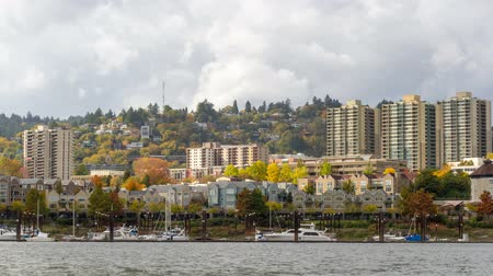 Time lapse movie of moving clouds over residential homes and condominiums in downtown Portland Oregon along Willamette River waterfront with boats during colorful fall autumn season 4096x2304
