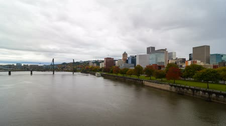 Time lapse movie of moving clouds over downtown city skyline of Portland Oregon along Willamette River with Hawthorne bridge one autumn fall season day 4k uhd