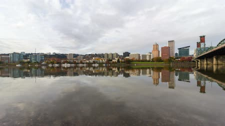 Ultra high definition 4k time lapse movie of moving clouds with clear water reflection over downtown city skyline of Portland Oregon along Willamette River with Hawthorne bridge one autumn fall season day 4096x2304 Стоковые видеозаписи