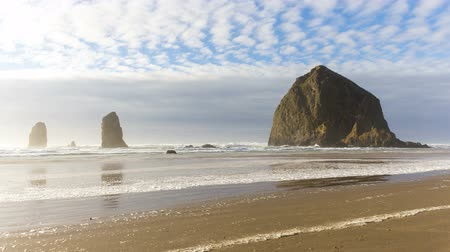 Ultra high definition 4k time lapse movie of clouds and sky over famous Haystack Rock with water reflection at low tide along Pacific Ocean in Cannon Beach Oregon 4096x2304 uhd Стоковые видеозаписи
