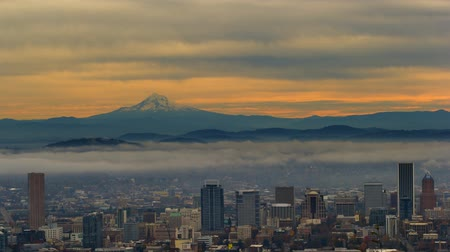 Ultra high definition 4k time lapse movie of moving clouds and low fog over cityscape of downtown Portland Oregon and snow covered mt. hood one early morning at sunrise 4096x2304 uhd