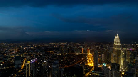 bakış : Ultra high definition 4k time lapse movie of moving clouds and aerial view of city transportation traffic in Kuala Lumpur Malaysia from daylight into blue hour evening into night lights 4096x2304 uhd