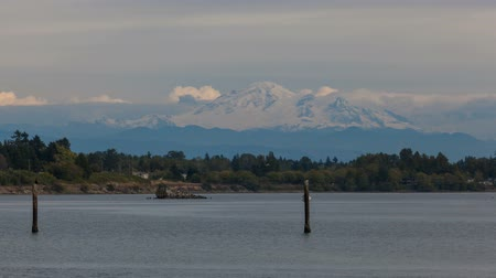 Time lapse of rolling white clouds over snow covered Mt. Baker along Semiahmoo Bay in Washington state USA 4k uhd