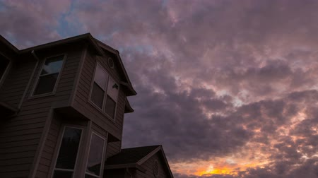 Colorful sunset and moving dramatic clouds over roof of residential suburb home in Happy Valley Oregon 4k ultra high definition time lapse video